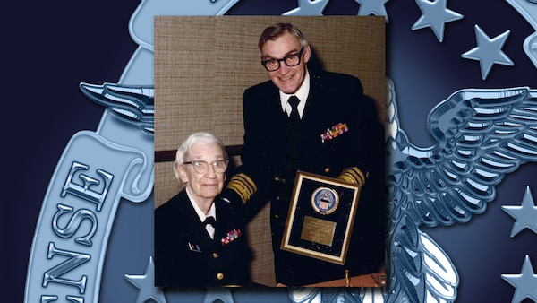 Man in dress Navy uniform holds a plaque he's presenting to a woman in a Navy dress uniform.