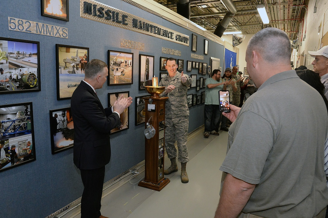 Eric Fox, Ogden Air Logistics Complex vice director, left, and Capt. Ryan VanArtsdalen, 583rd Missile Maintenance Squadron (MMXS) deputy commander, center, applaud the presentation of the LAMP award to members of the 583rd MMXS who attended the ceremony virtually from Malmstrom Air Force Base, Montana, March 11, 2020, at Hill Air Force Base, Utah. The squadron was recognized for its dedication to safety and accomplishing its production under extreme weather conditions. (U.S. Air Force photo by Alex R. Lloyd)