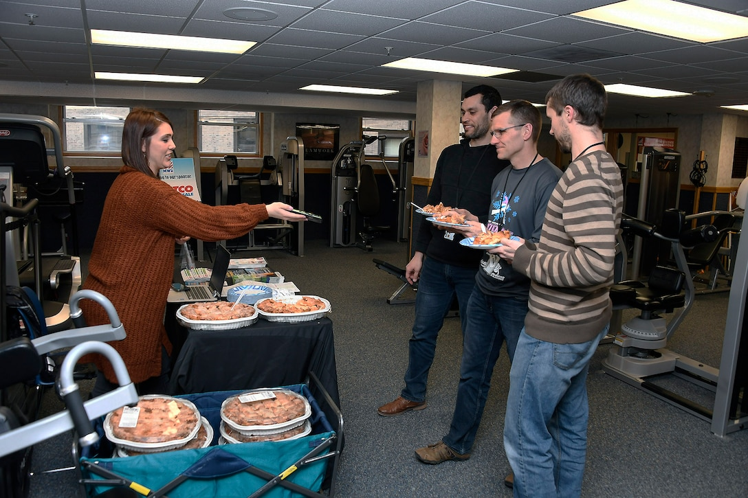 Cory William (left), Chad McKeever (middle) and Chris Ashbay (right) accept their post run apple pie from a sponsor rep after participating in the Pi Day observance March 11.