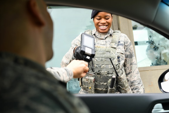 Airman Jaylin Borsh-Thomas, 22nd Security Forces Squadron entry controller, scans a common access card March 18, 2020, at McConnell Air Force Base, Kansas. As part of Team McConnell's efforts to ensure the safety and health of its members, new guidelines have been implemented base-wide to promote health protection of its members. Touch-free ID scanning, which has been effective since March 14, 2020, requires all members accessing the installation to display their ID for entry controllers to verify. (U.S. Air Force photo by Airman 1st Class Nilsa E. Garcia)