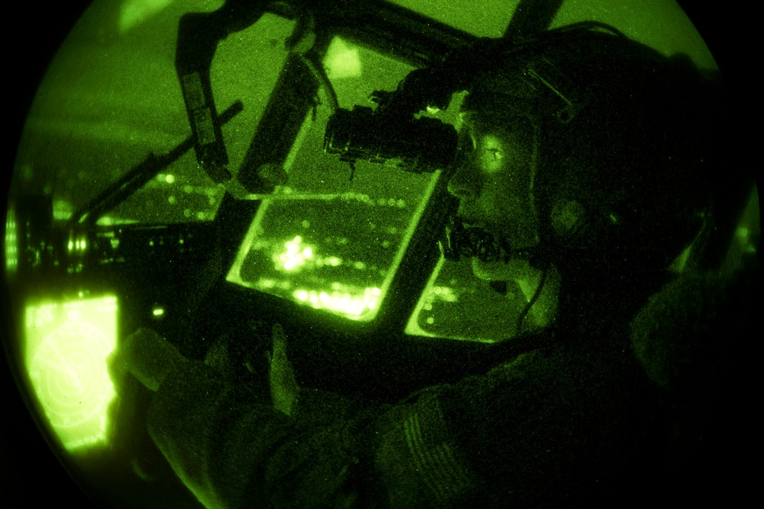 An Air Force pilot wearing a night-vision device flies a plane at night, illuminated by green light.
