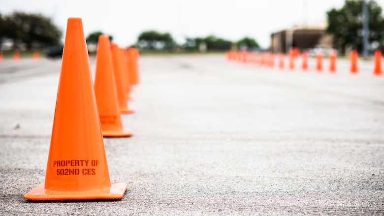 Cones are lined up March 19, 2020 in preparation for the opening of a drive-through screening and testing line beginning March 20, 2020 at Joint Base San Antonio-Lackland, Texas. The line will be open 9 a.m. to 2 p.m. Monday through Friday for anyone experiencing flu-like symptoms prior to entering Wilford Hall Ambulatory Surgical Center. (U.S. Air Force photo by Tech. Sgt. Katherine Spessa)
