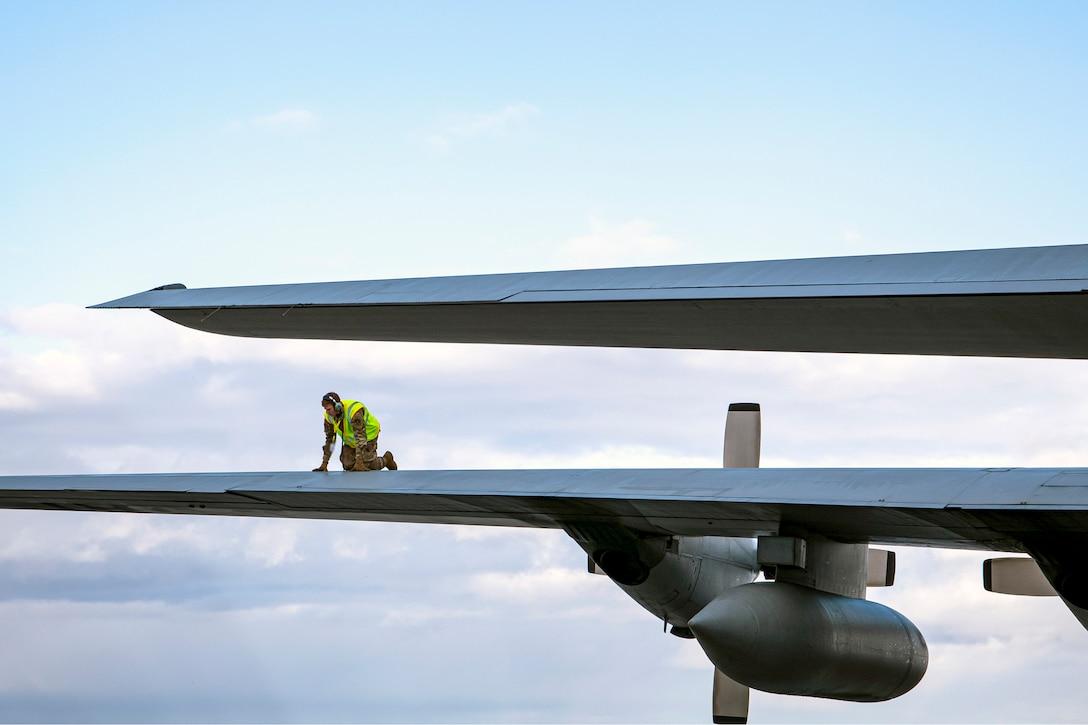 An airman kneels atop an aircraft wing.