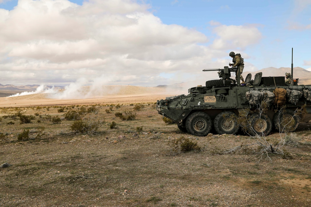 A soldier works on a machine gun atop a military vehicle.