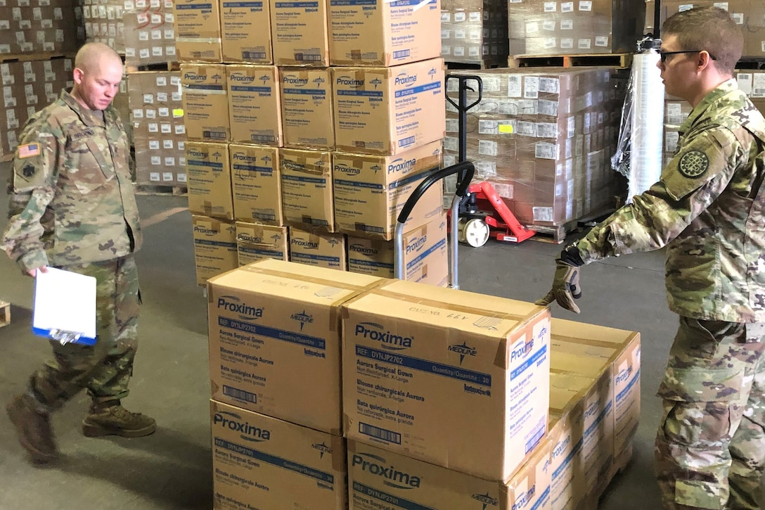 Soldiers use a hand truck to move stacks of boxes.