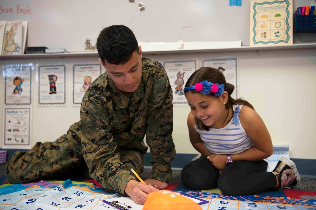A Marine writes on a piece of paper while a young child smiles and watches.