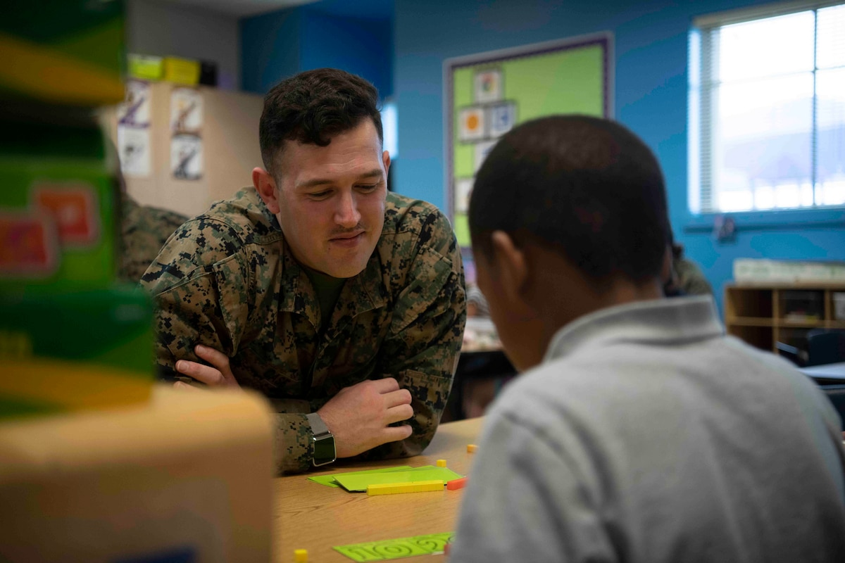 A Marine watches a young boy working in a school room.