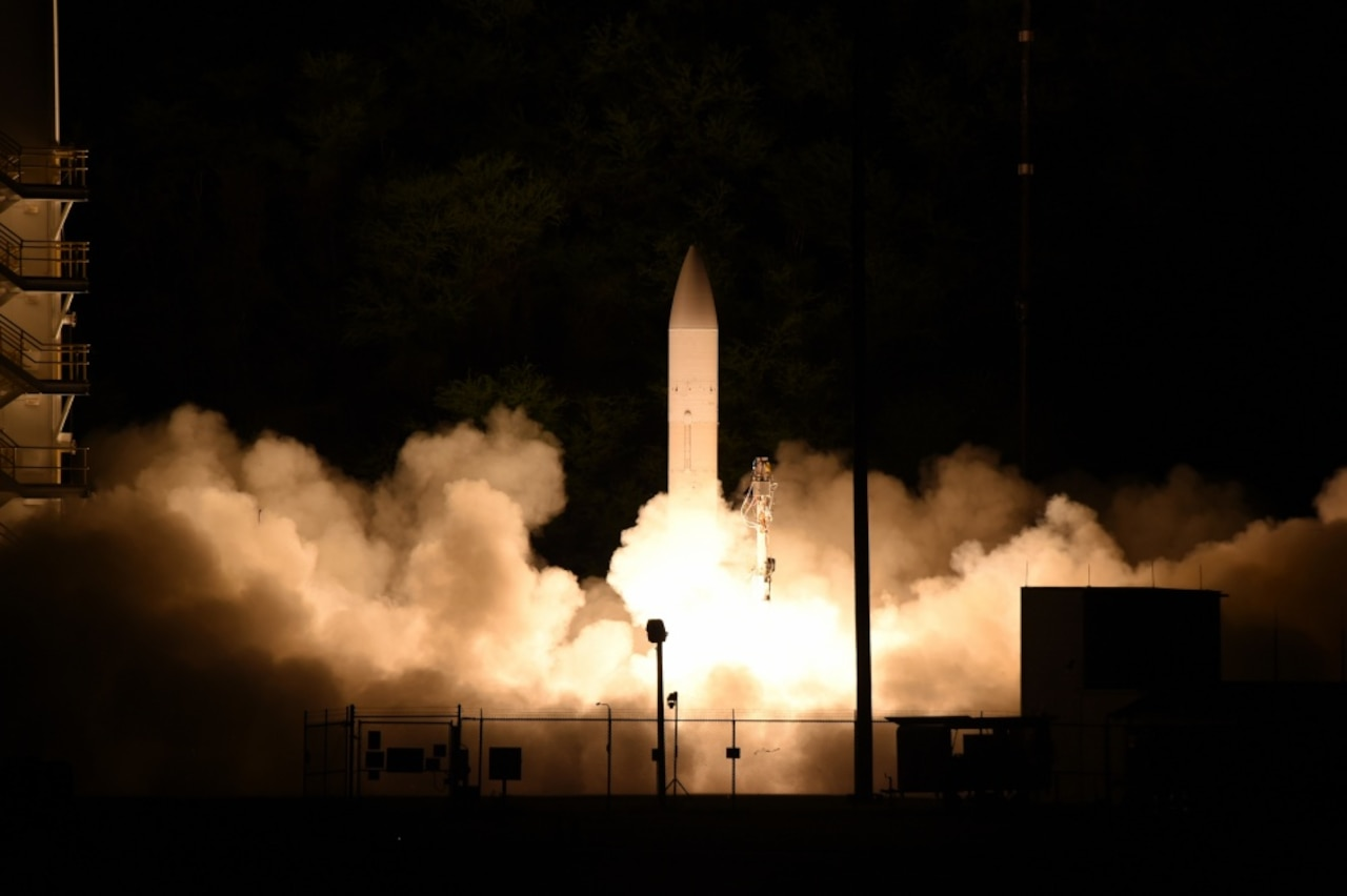 A nighttime missile launch with black sky and white smoke surrounding the missile.