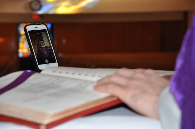 Hand of a chaplain on a bible with a smart photo recording a mass with empty pews.