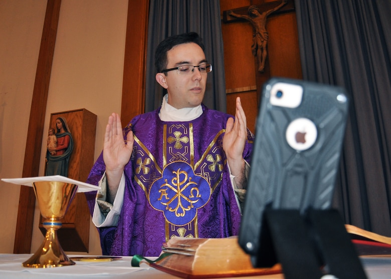priest at alter preparing the gifts offered before communion during a virtual mass with a cell phone in foreground.