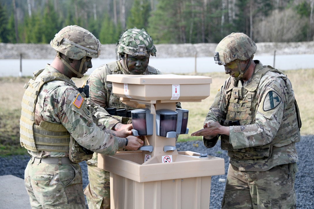Soldiers use a field hand-washing station to protect themselves against the coronavirus.