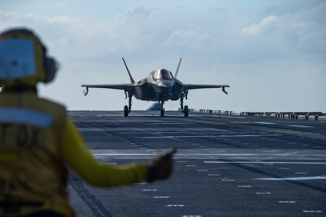 An F-35B Lightning II fighter aircraft is cleared for takeoff by a U.S. Sailor aboard amphibious assault ship USS America March 18.