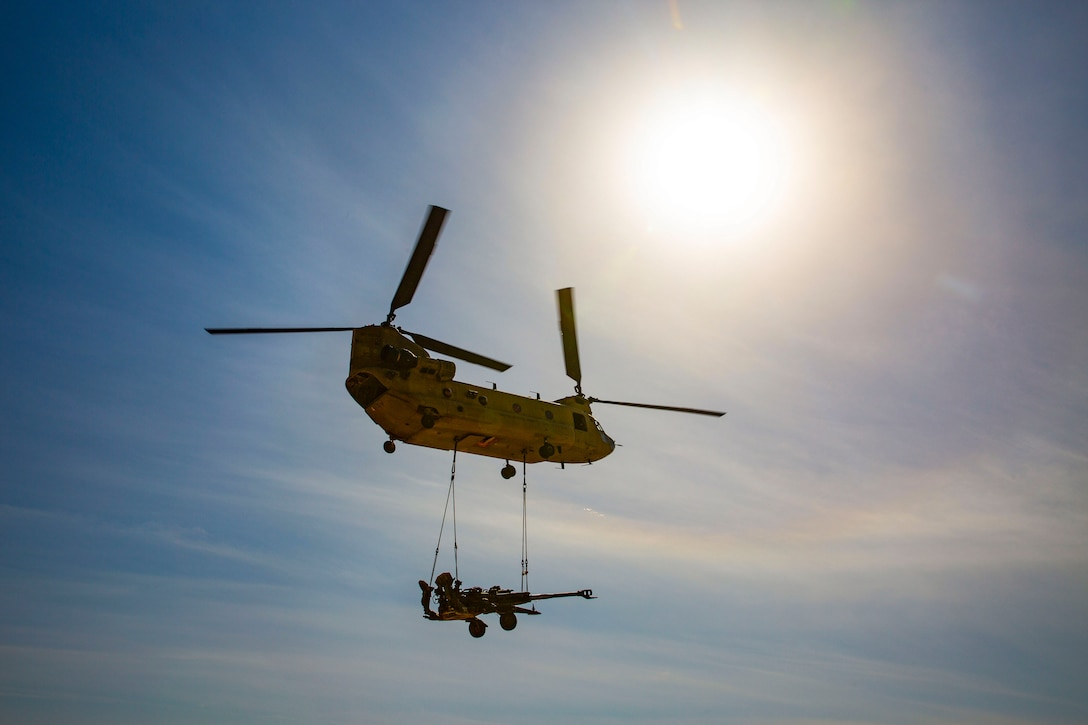 A helicopter flies with a howitzer suspended below it by ropes.