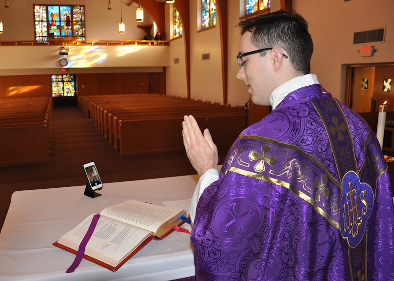 priest at altar reading the gospel, with empty pews in the background while recording virtual mass with a cell phone.