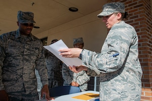 Photo of an Airman briefing Stop, Check, Go volunteers.