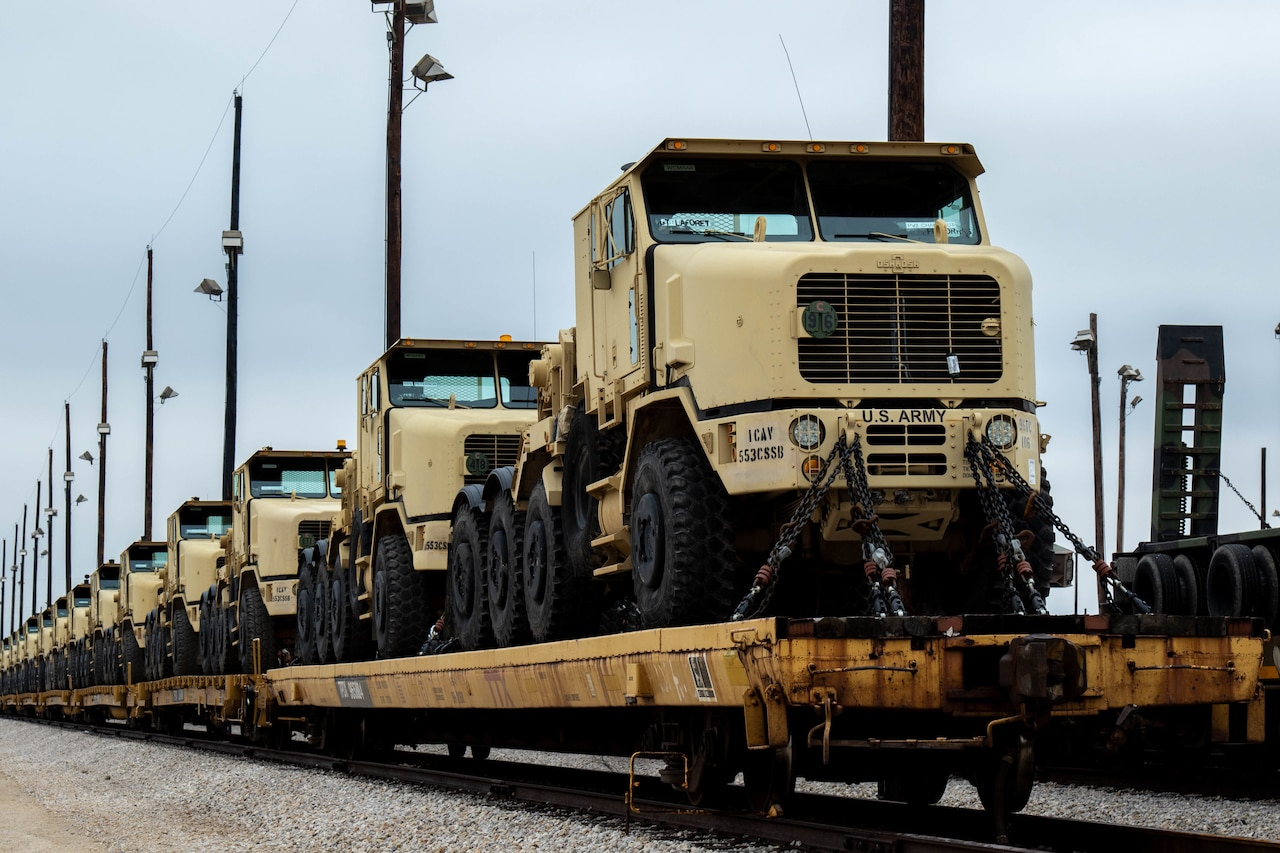Military vehicles are loaded atop rail cars.