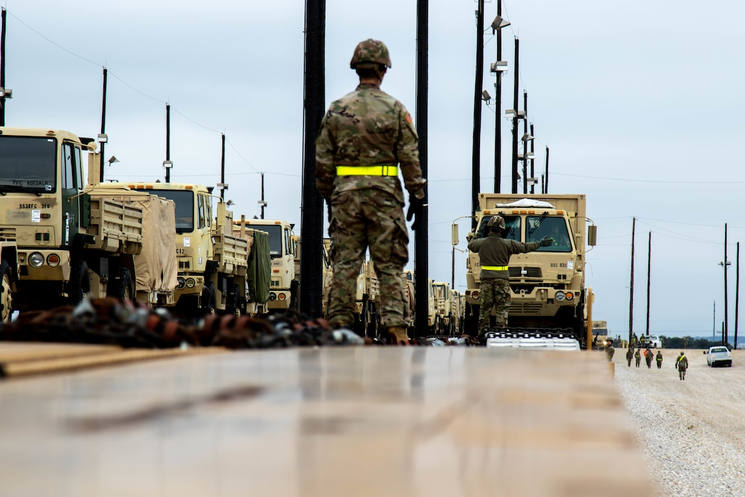 A military person guides the transport of military vehicles in a rail yard.