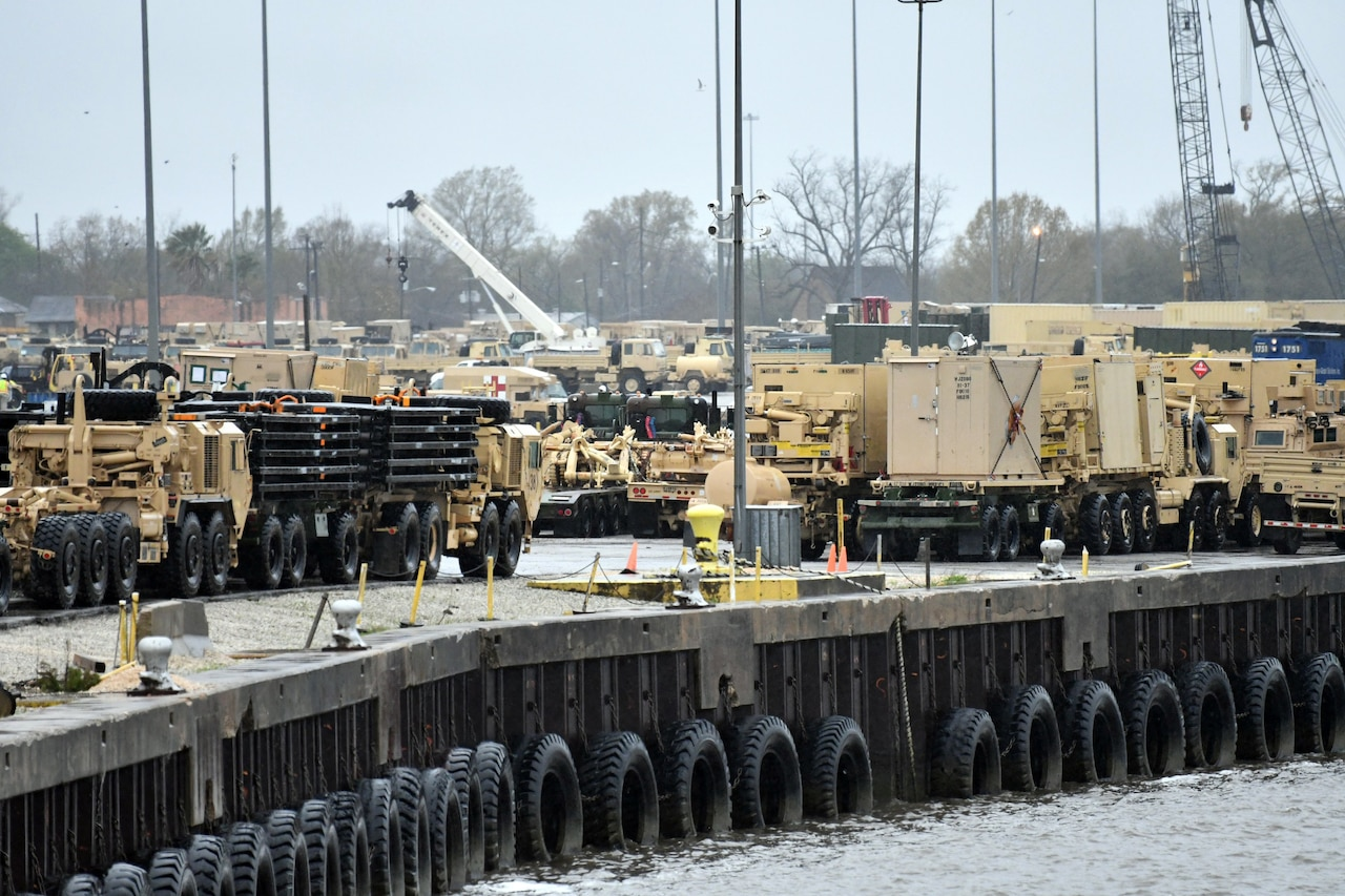 Dozens of military vehicles are marshalled at a port.