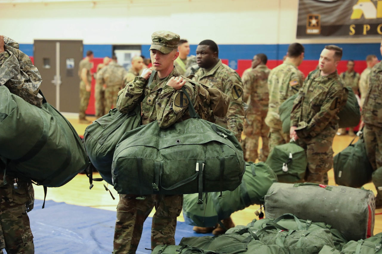 Service members carry mobility bags indoors.