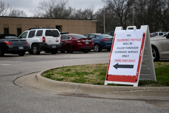 A sign located at the entrance of the 509th Medical Group, directs pharmacy patients to the new curb side pharmacy pickup at Whiteman Air Force Base, Missouri, March 20, 2020. The medical group's pharmacy implemented curbside pickup pharmacy procedures. The new service allows individuals with called-in refills and activated prescriptions to park in a designated parking spots and have their prescriptions delivered to the car. This procedure is part of the effort to limit visiting the facility. (U.S. Air Force photo by Staff Sgt. Dylan Nuckolls)