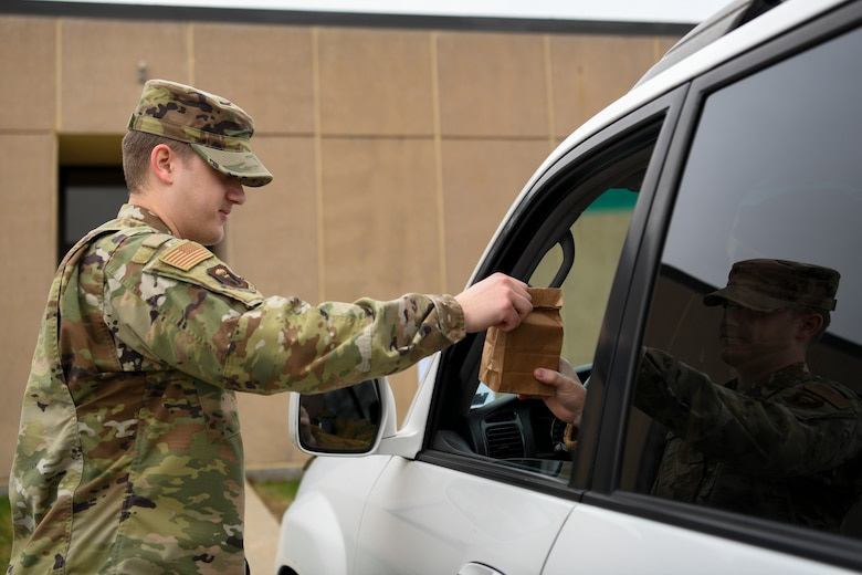 U.S. Air Force Staff Sgt. Nathan Jones, a 509th Operational Medical Readiness Squadron bioenvironmental technician and pharmacy augmentee, delivers prescriptions to a patient outside the 509th Medical Group, at Whiteman Air Force Base, Missouri, March 20, 2020. The medical group's pharmacy implemented curbside pickup pharmacy procedures. The new service allows individuals with called-in refills and activated prescriptions to park in a designated parking spots and have their prescriptions delivered to the car. This procedure is part of the effort to limit visiting the facility. (U.S. Air Force photo by Staff Sgt. Dylan Nuckolls)