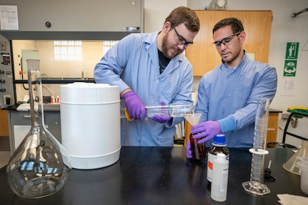 Code 134, Laboratory Division, chemists Anthony Painter, left, and Deniz Ferrin, right, make hand sanitizer March 20, 2020, inside the Puget Sound Naval Shipyard & Intermediate Maintenance Facility chem lab in Building 59. (PSNS & IMF photo by Scott Hansen)