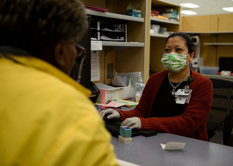 A pharmacist technician speaks for a patient at a desk.