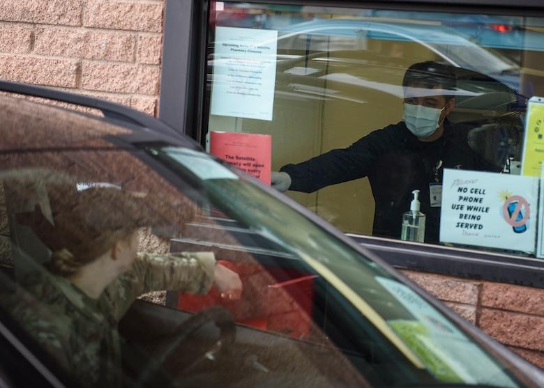 A pharmacist technician passes prescriptions to an Airman through the drive-thru.