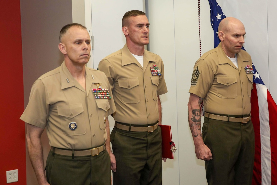 Maj. Gen. Matthew G. Glavy, Sgt. Maj. Daniel L. Krause and Sgt. Maj. Jay D. Williamson stand at attention during a relief and appointment ceremony in Lasswell Hall, Fort Meade, Maryland, Mar. 19, 2020. Krause relinquished his duties as the sergeant major of Marine Corps Forces Cyberspace Command, while Sgt. Maj. Jay D. Williamson was appointed to fill the role. (Department of Defense photo by Joseph Wilbanks)