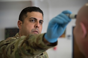 New Jersey Air National Guard Tech. Sgt. Emilio E. Gonzalez, a 108th Medical Group public health technician, administers a temperature screening to a Security Forces Airman at Joint Base McGuire-Dix-Lakehurst, New Jersey, March 19, 2020. The Medical Group screened members for possible fever, a common symptom of COVID-19, before being put on state active duty orders. (U.S. Air National Guard photo by Airman 1st Class Andrea A. S. Williamson)