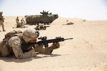 A group of Marines aim weapons in a dirt area.