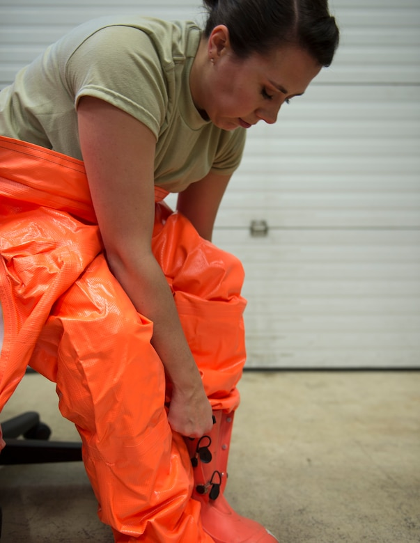 U.S. Air Force Senior Airman Morgan Johnson, an emergency manager with the 133rd Civil Engineer Squadron, puts on a HAZMAT suit in St. Paul, Minn., March 11, 2020.