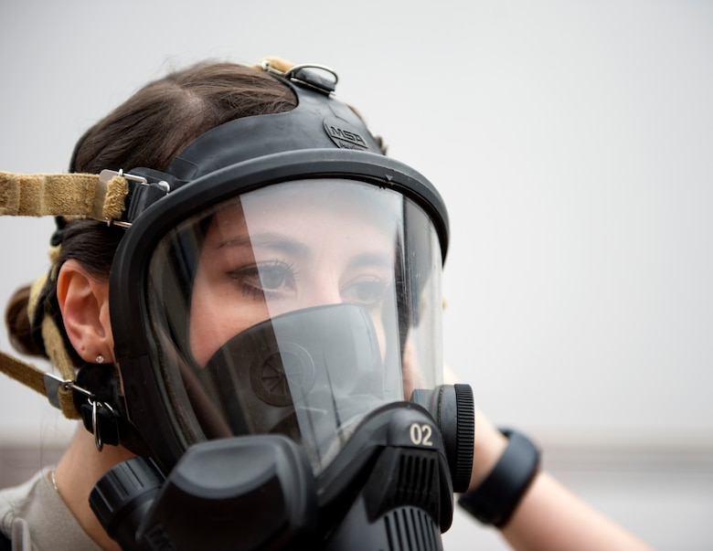 U.S. Air Force Senior Airman Morgan Johnson, an emergency manager with the 133rd Civil Engineer Squadron, puts on a Fire Hawk M7 Air Mask in St. Paul, Minn., March 11, 2020.