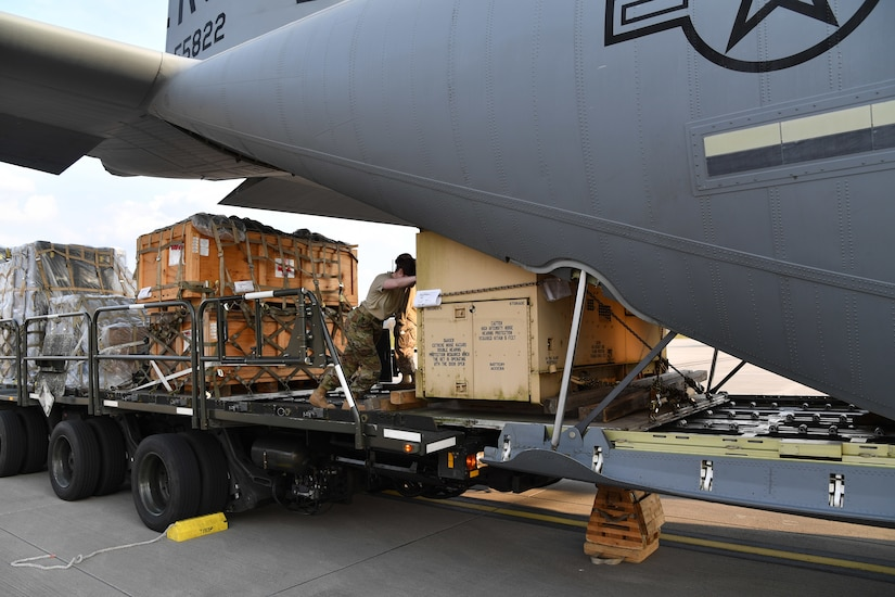 Airmen push a pallet of cargo up the loading ramp of a transport aircraft.