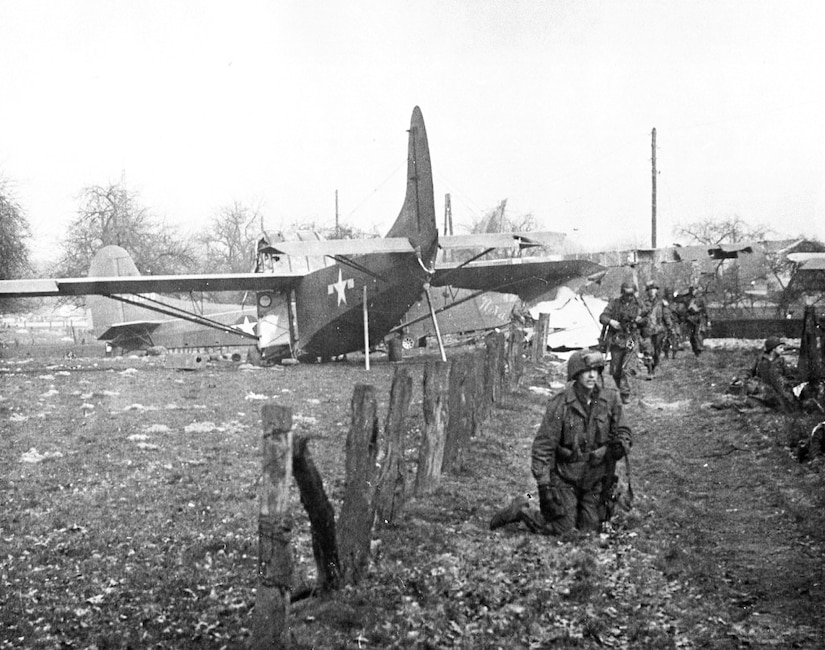 Troops move down a dirt road away from an airplane.