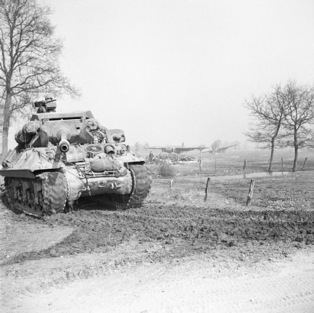 A tank moves down a dirt road.
