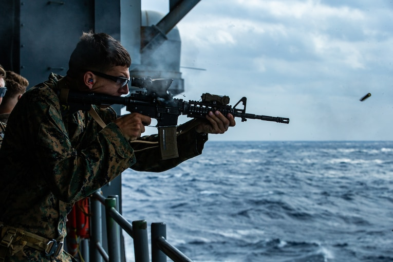 A Marine fires a service rifle over water from aboard a ship.