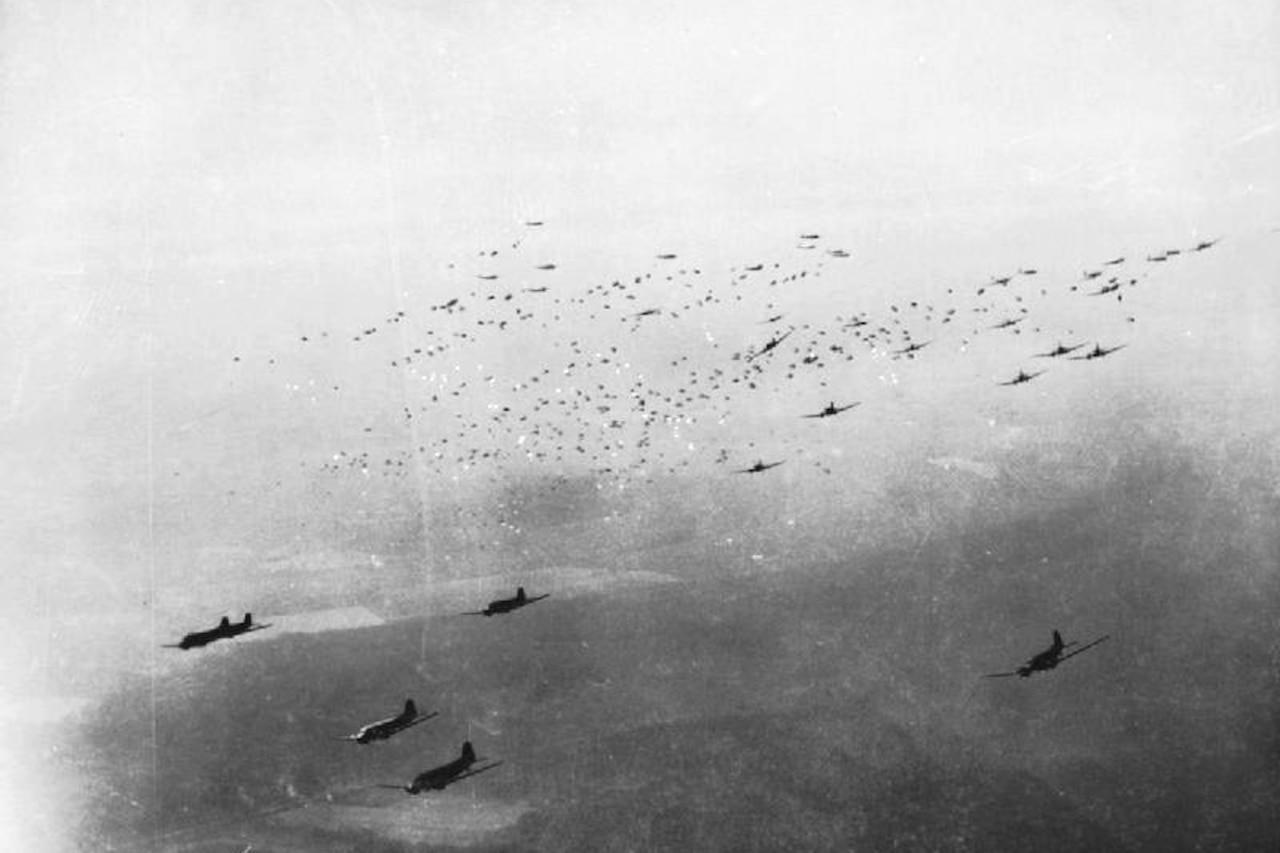 Planes drop paratroopers.
