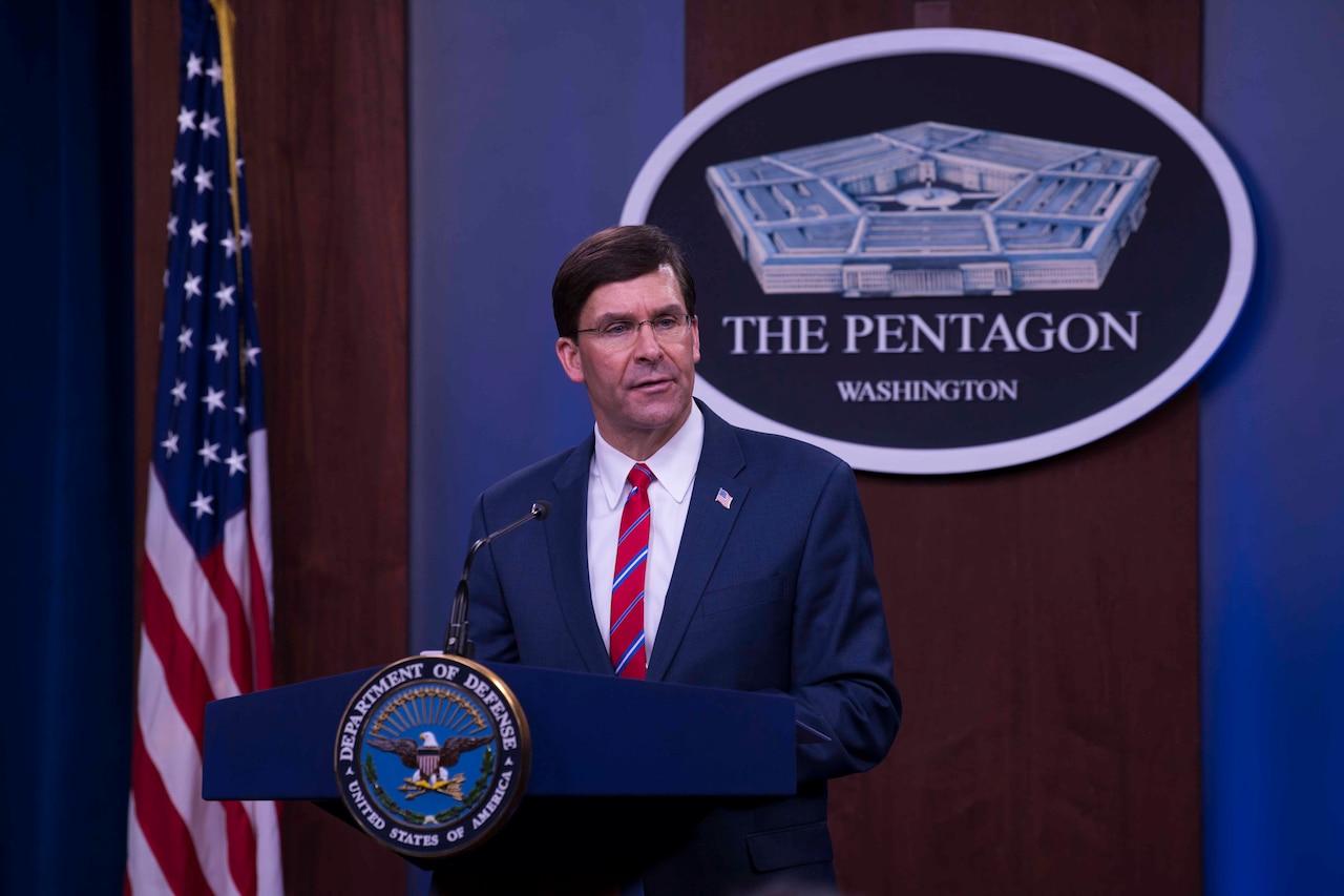 Defense Secretary Dr. Mark T. Esper stands behind a podium.