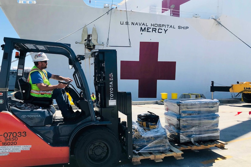 In the foreground, a forklift moves supplies. Behind the forklift is a Navy ship.