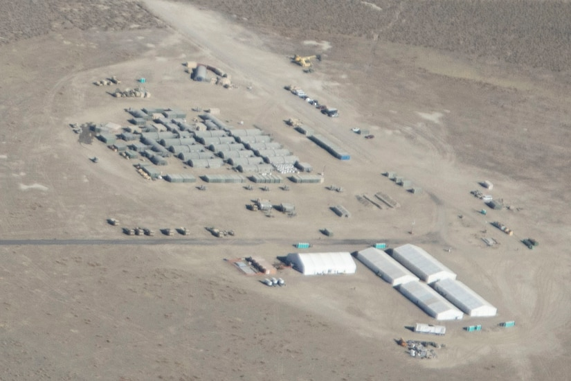 An aerial photo shows a field hospital with many tents spread out across a desert environment.