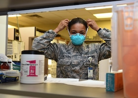 U.S. Air Force Staff Sgt. Montea Armstrong, 17th Medical Group pharmacy technician, applies proper protective gear for heightened exposure risks with customer interactions at the Ross Clinic's pharmacy on Goodfellow Air Force Base, Texas, March 23, 2020. With Goodfellow's Health Protection Condition in BRAVO, Armstrong wore a mask to avoid contamination of COVID-19. Goodfellow currently has no confirmed COVID-19 cases. (U.S. Air Force Photo by Airman 1st Class Abbey Rieves)
