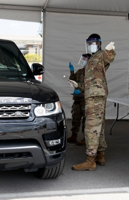 Florida Army National Guard Soldiers from the 1218th Transportation Company, West Palm Beach, scribe patient information during COVID-19 testing at Hard Rock Stadium in Miami Gardens March 23, 2020. The testing site is the second set up by the Guard in South Florida.