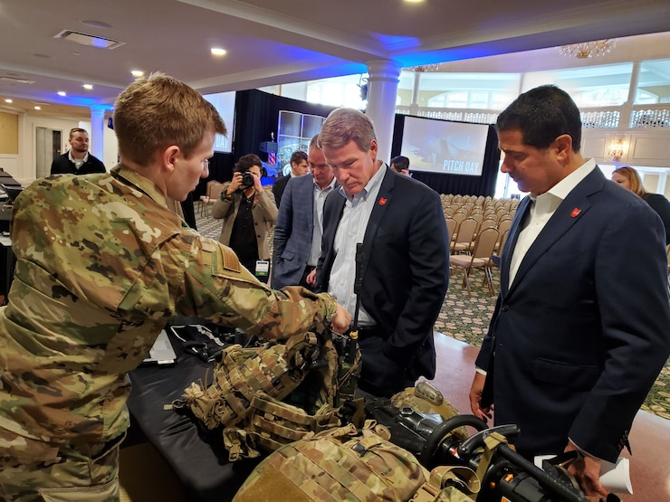 1st Lt Patrick Assef (left) a special warfare mechanical engineer with the Air Force Research Laboratory, explains several Air Force programs to Lt. Governor Jon Husted (center) of Ohio during the Air Force Life Cycle Management Center's Pitch Day Nov.13-14, 2019