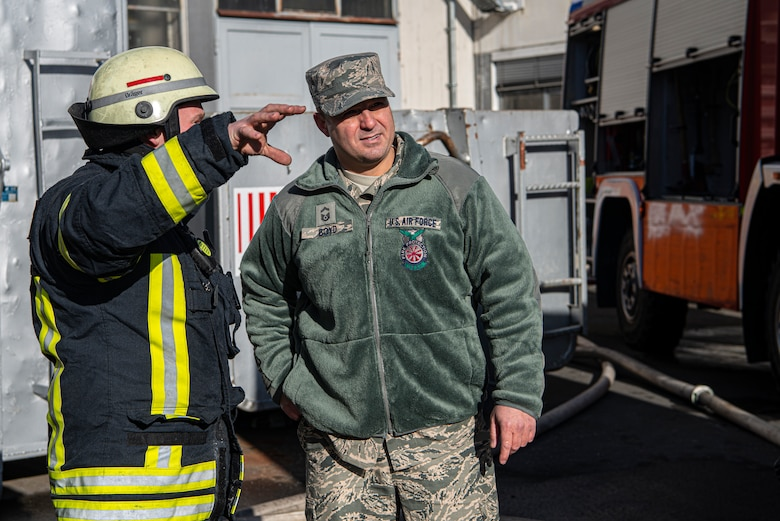 U.S. Air Force Senior Master Sgt. Jordan Boyd, 86th Civil Engineer Squadron Fire and Emergencies deputy fire chief, speaks with a German firefighter on-scene in Otterberg, Germany, March 23, 2020.