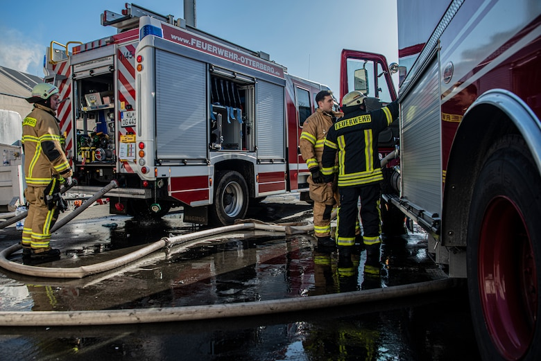 Three firefighters prepare to attach hoses from one truck to the other in Otterberg, Germany, March 23, 2020.
