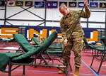 Sgt. Ryan Goyette, 197th Field Artillery Brigade, New Hampshire Army National Guard, sets up one of approximately 250 beds at the Stan Spirou Field House at Southern New Hampshire University in Hooksett, Mar. 23.