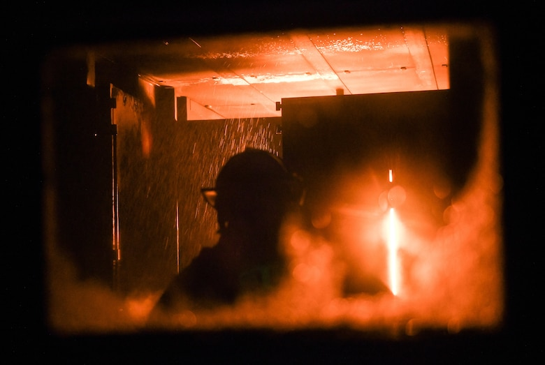 A firefighter stands in a live fire training simulator at Arnold Air Force Base, Tenn., Feb. 25, 2020. Propane fuels the fires in the simulator. (U.S. Air Force photo by Jill Pickett)