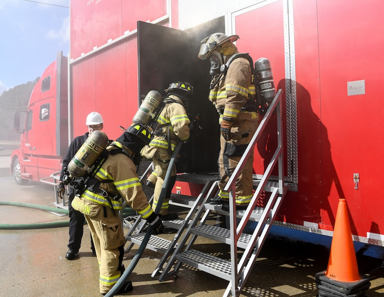 Arnold Air Force Base Fire and Emergency Services personnel enter a live fire trainer Feb. 25, 2020, at Arnold AFB, Tenn. during a training exercise. The trainer is a mobile trailer brought to the base for training. It uses propane for the fuel and simulated smoke, providing a more controllable situation for training. (U.S. Air Force photo by Jill Pickett)