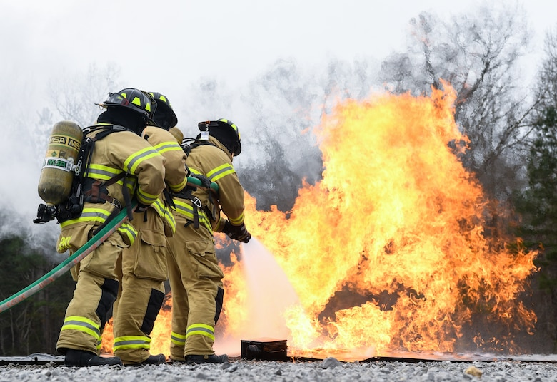 Arnold Air Force Base Fire and Emergency Services personnel attack a ground fire near an aircraft with a hand line while training, March 5, 2020, using a propane-fueled trainer brought to the base. The aircraft trainer uses propane to generate controlled fires in various locations in and around the mock fuselage. (U.S. Air Force photo by Jill Pickett)
